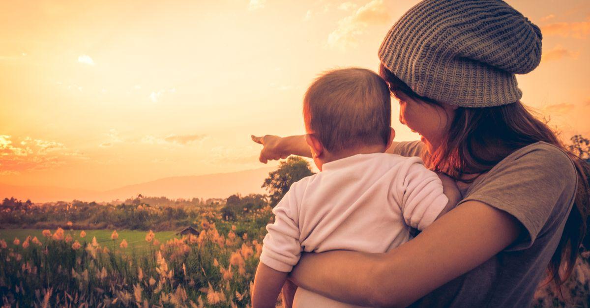 Mutter schaut mit Baby in Sonnenuntergang