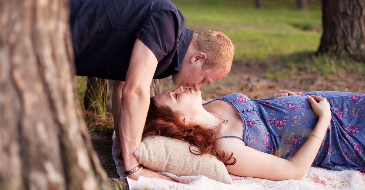 Mann küsst schwangere Frau im Park