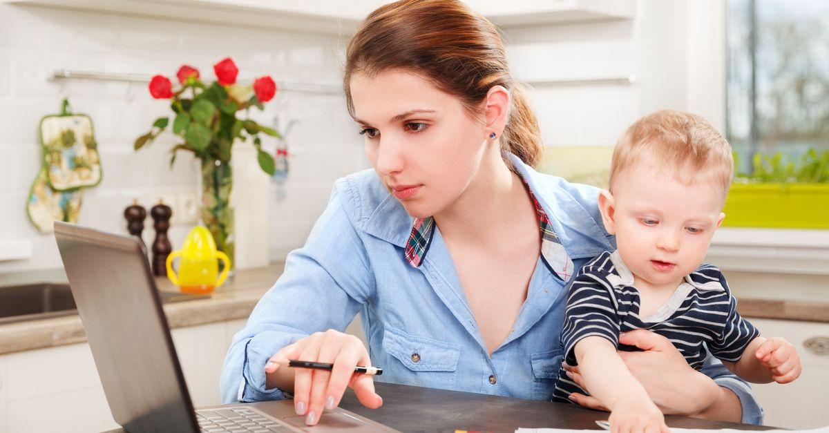 Mutter mit Baby am Schoß beim Lernen