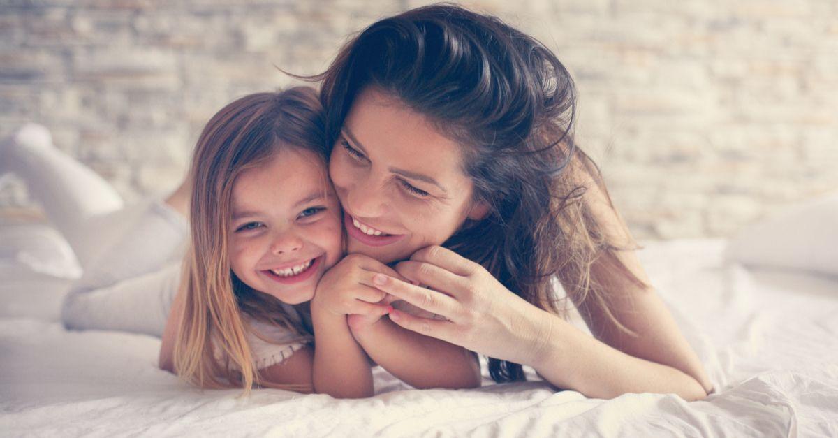 Mutter mit Kind kuschelt und lacht