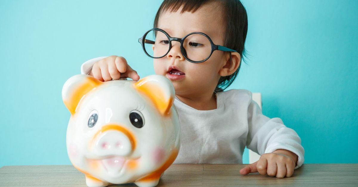 Baby schmeißt Geld in Sparschwein